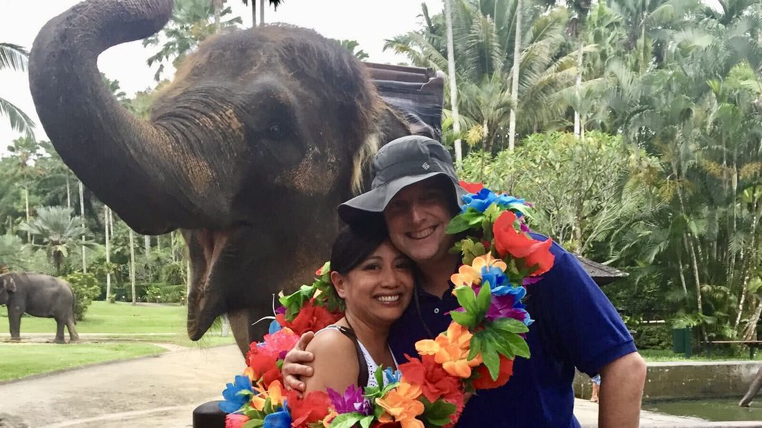 Financial planner and her husband posing by an elephant