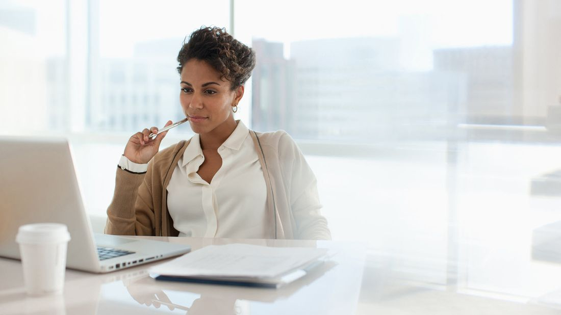Businesswoman looking at her computer as she attempts to avoid leaving money on the table as she is changing jobs.