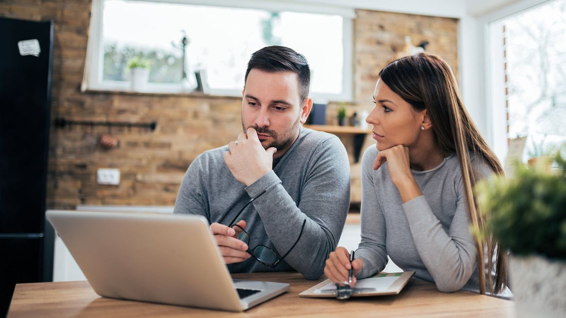Husband and wife looking at computer reading tips for financial uncertainty.