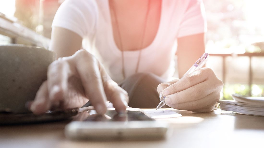 A woman doing her taxes with a pen and cell phone