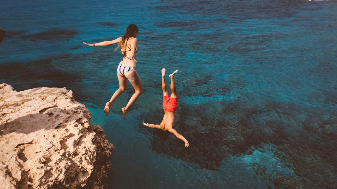 couple jumping off cliff into water