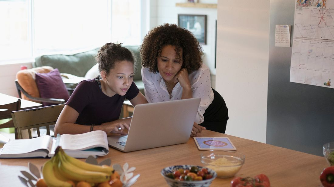 mom and daughter working on FAFSA in kitchen