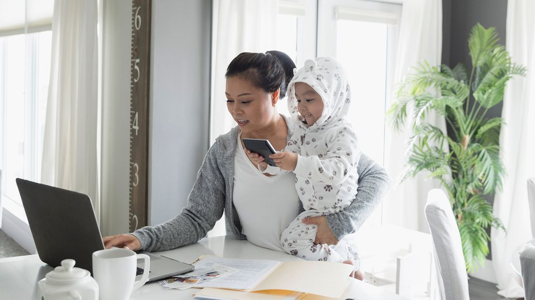 mom working from home while holding toddler in pajamas