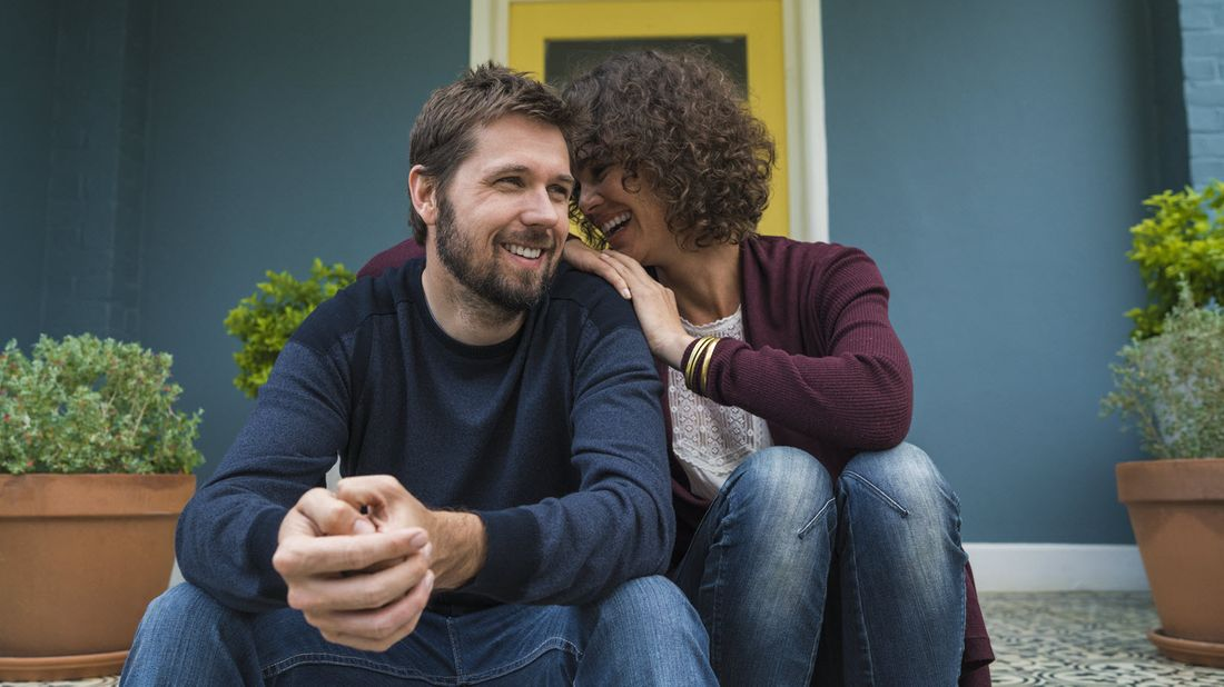 Couple sitting in front of house.