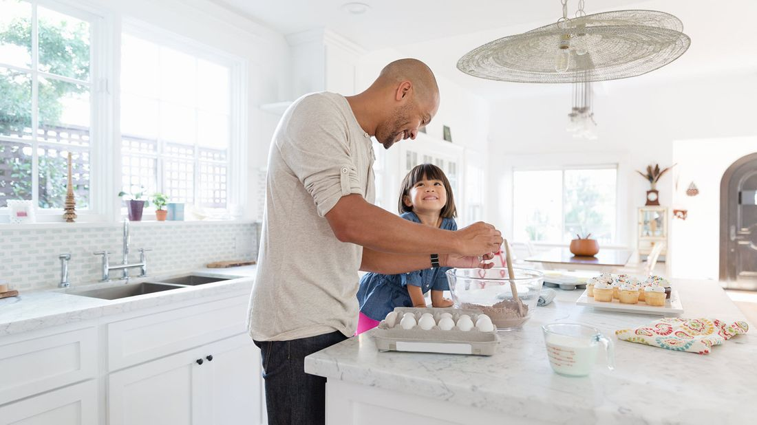 Father and daughter making cupcakes together.