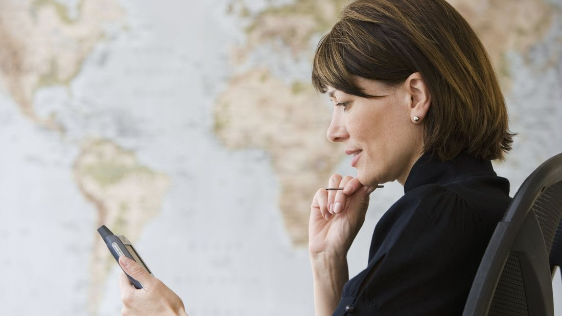 A woman reading her phone in front of a world map