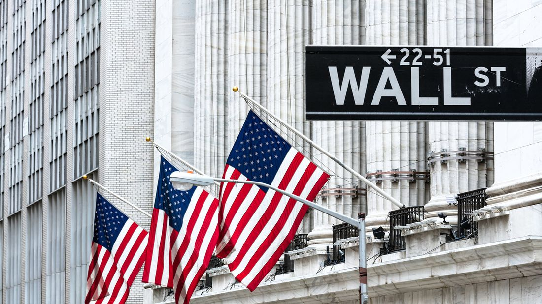 New York Stock Exchange with American flags and Wall Street sign