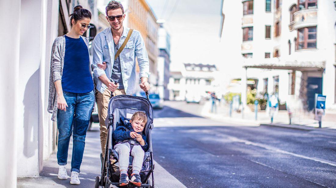 couple pushing toddler in stroller on city street
