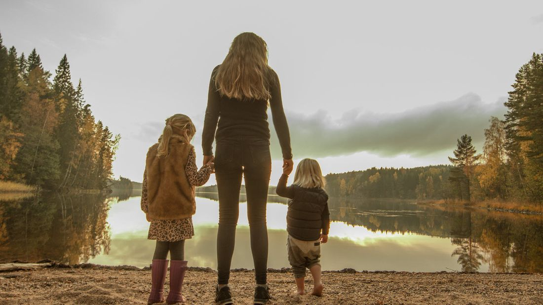 Mother and her daughters looking at a lake.
