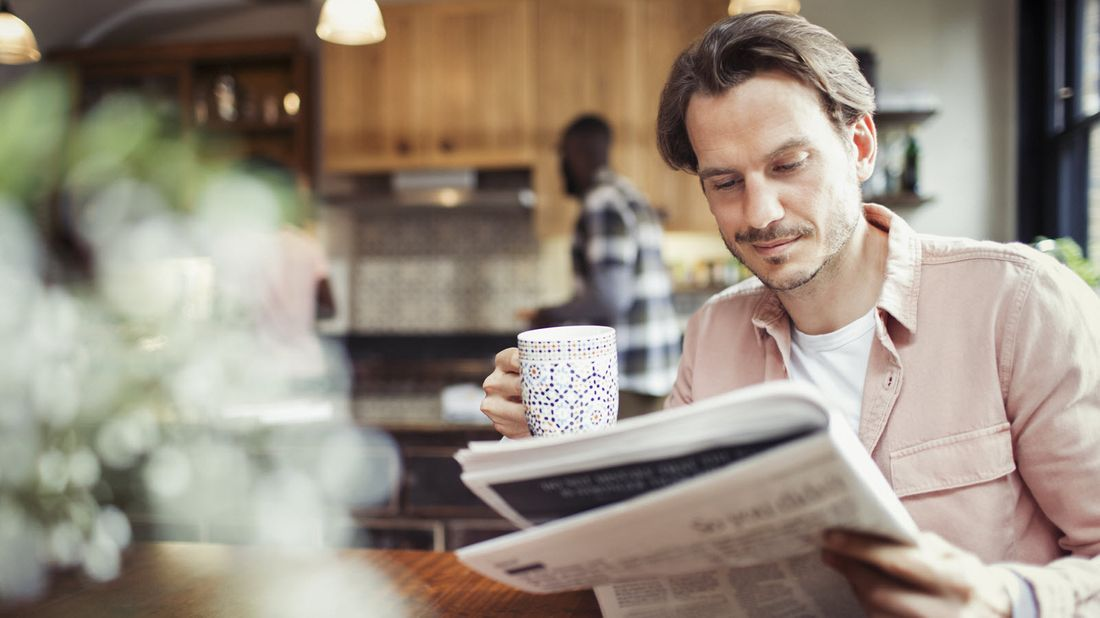 A man reading the newspaper and drinking coffee
