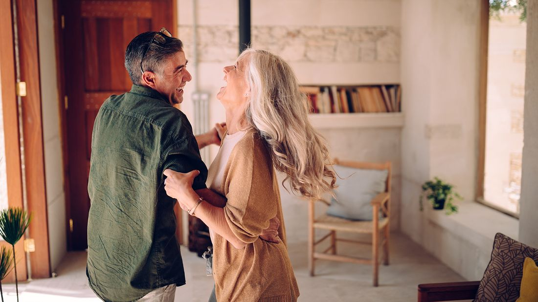 happy senior couple dancing in living room
