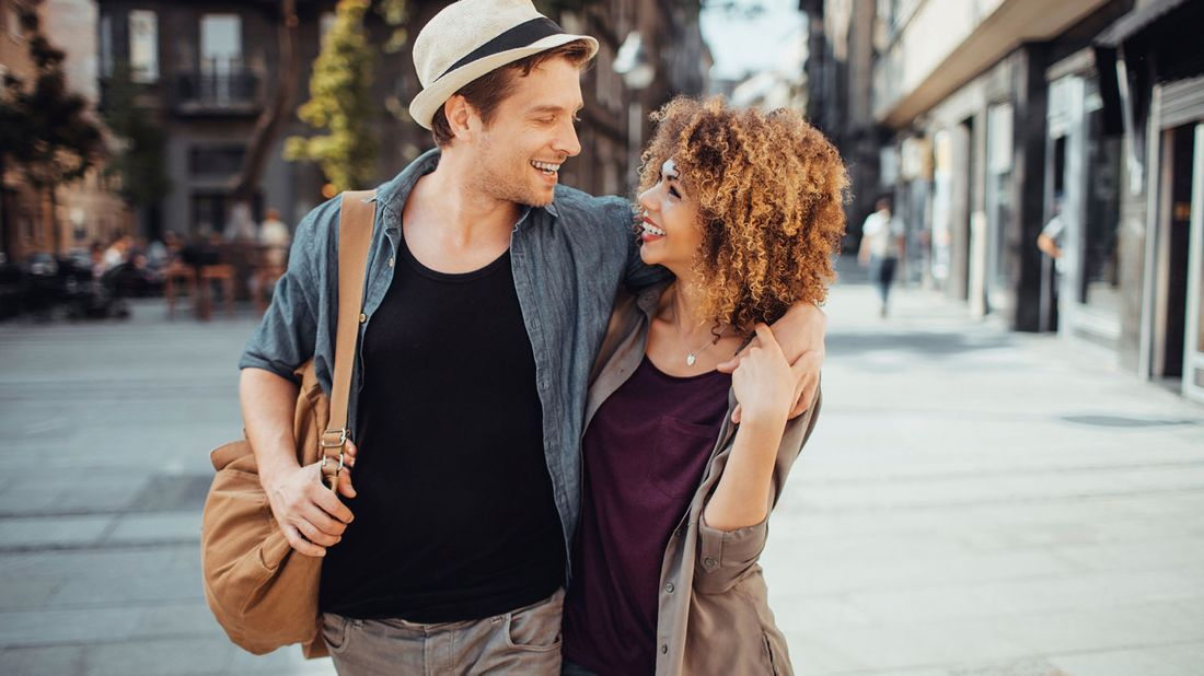couple walking on street with arms around each other