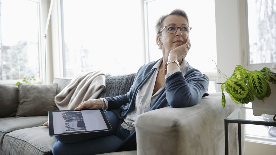 Woman on couch with tablet wondering what happens to the money in an annuity when you die.
