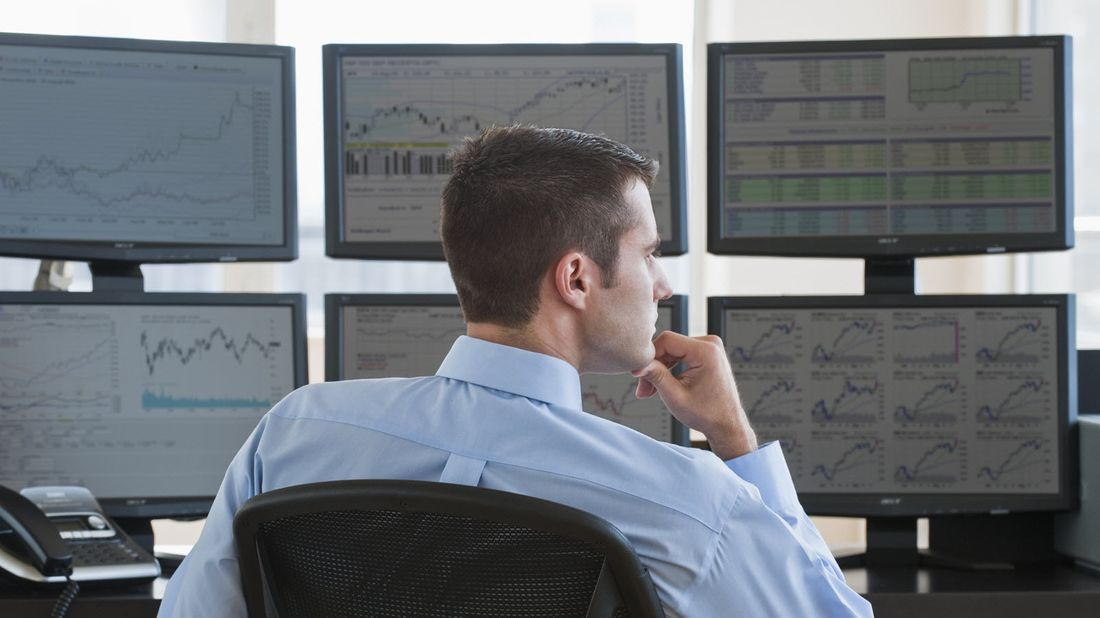 A man watching stock trading action on computer screens