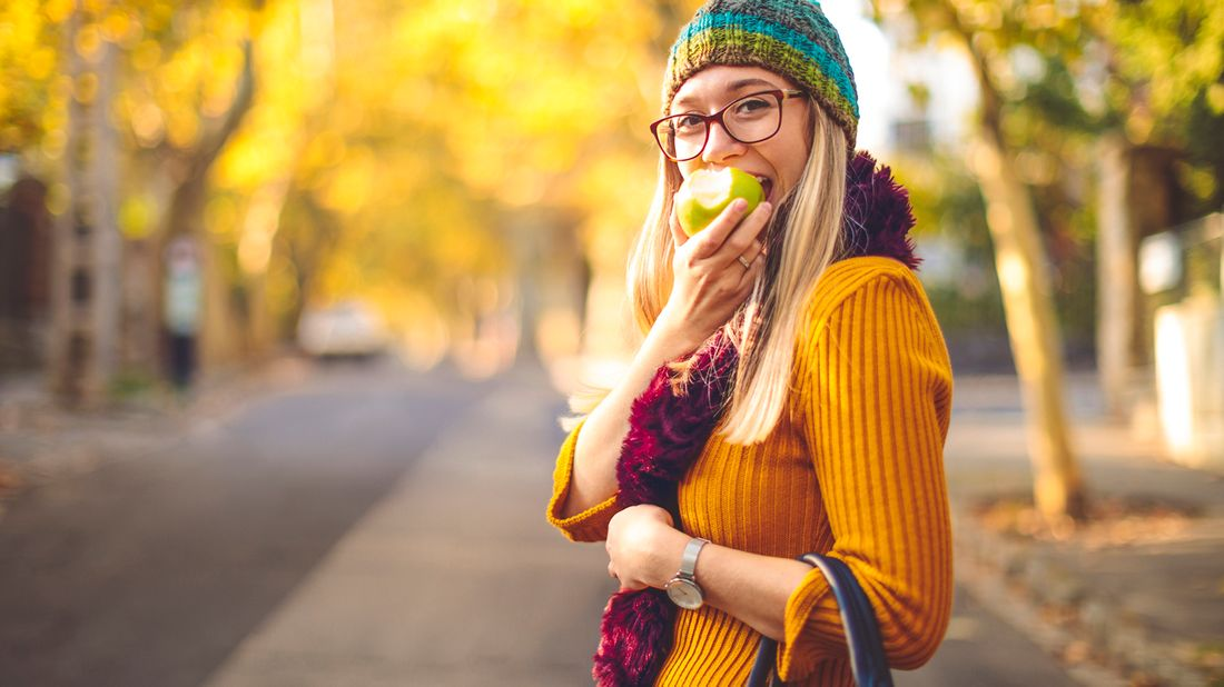 Woman eating apple thinking about what to buy and what to skip in October.