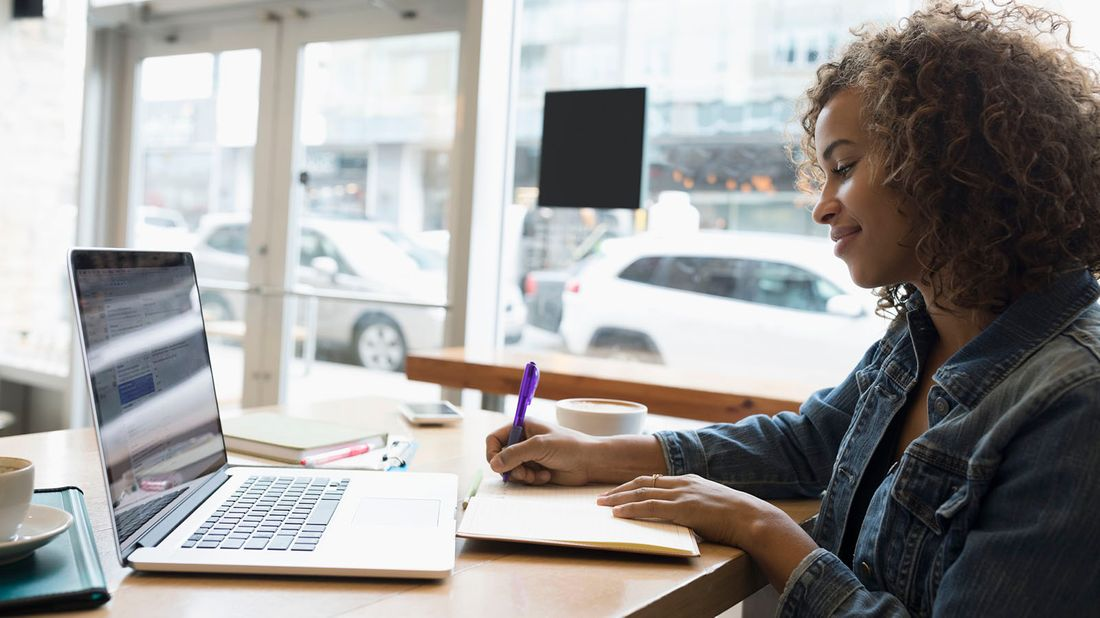 self-employed woman working on laptop researching benefits