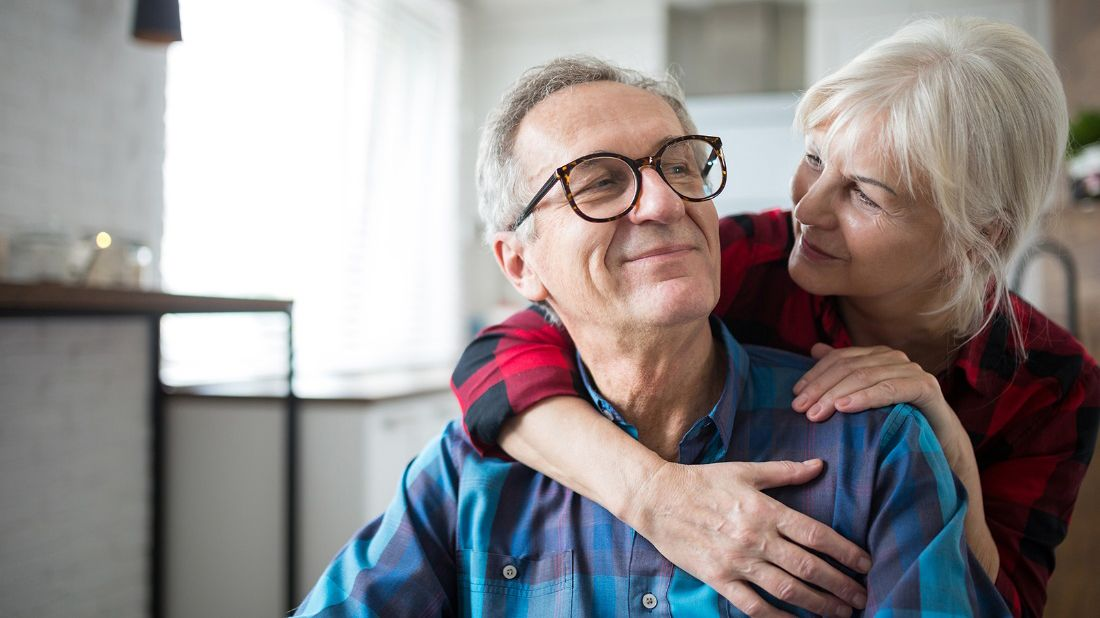 Senior man and woman hugging in their home discussing reverse mortgages.