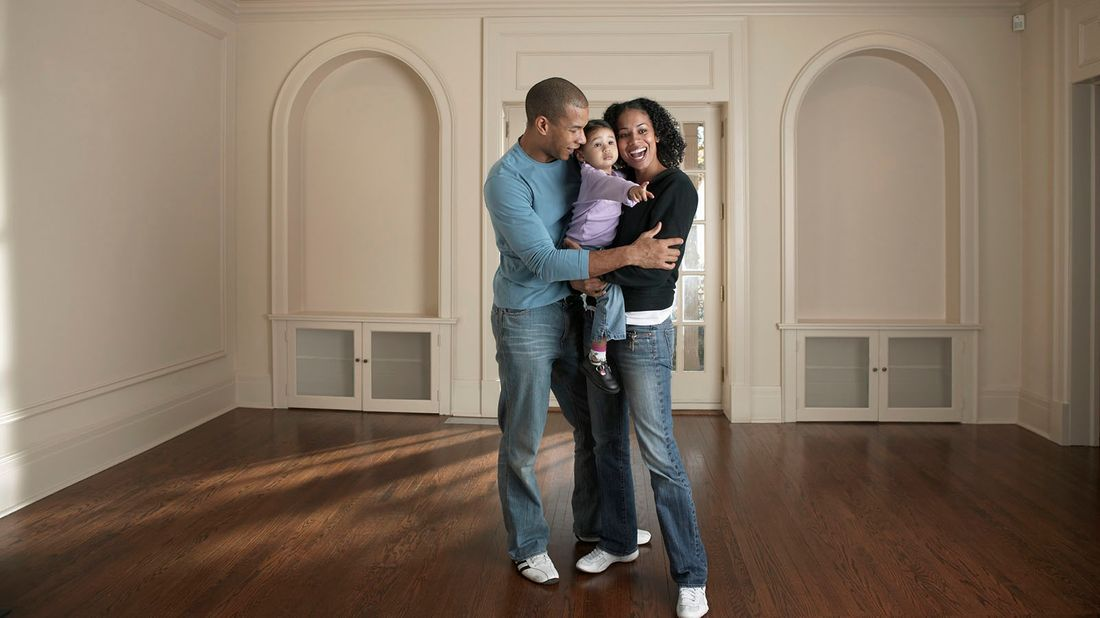 couple holding baby girl in a room while house hunting