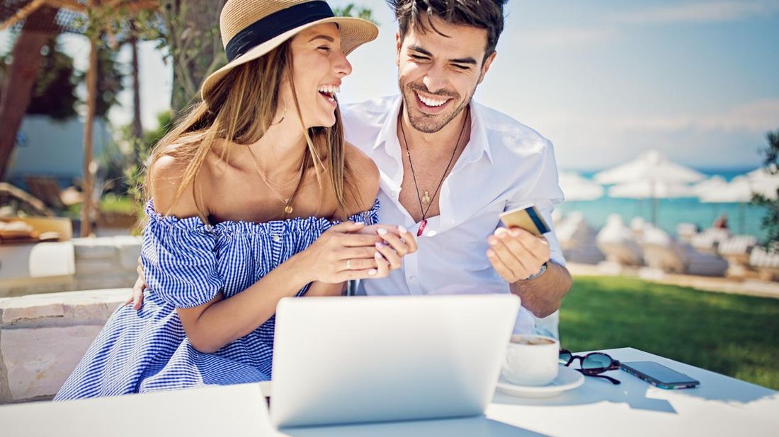 Young couple using a credit card to shop online.