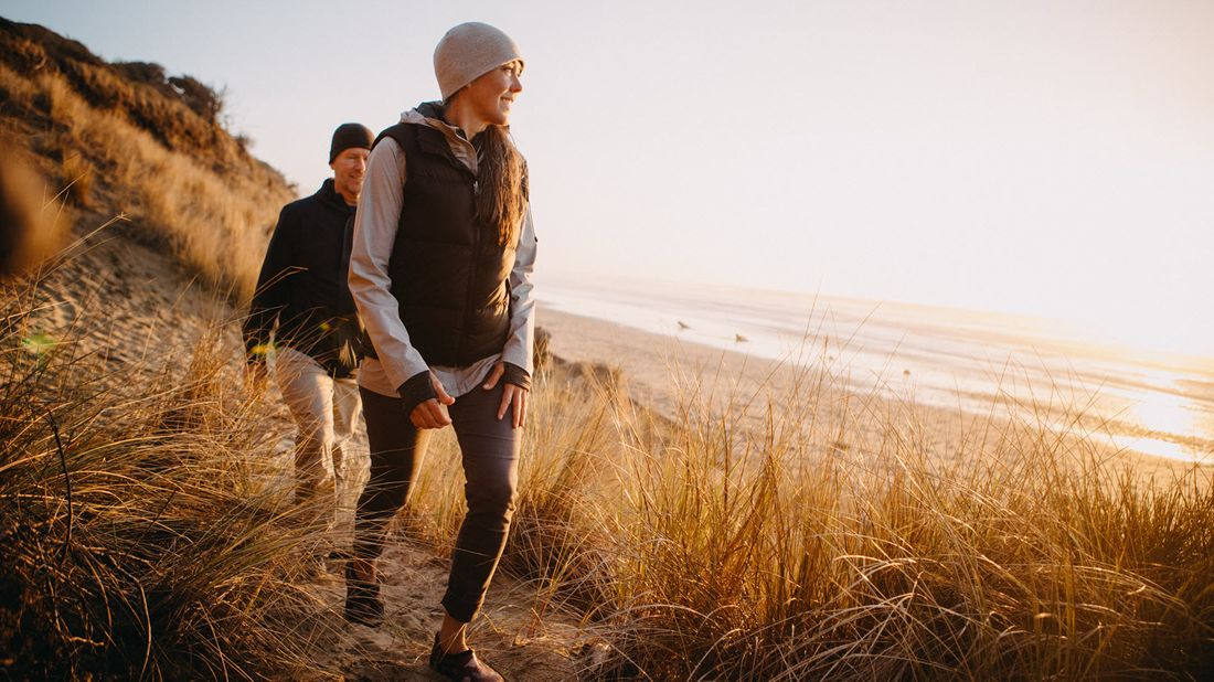 Couple hiking near the beach thinking about how much an average retirement costs.