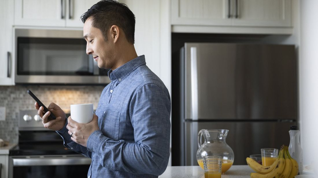Man drinking coffee and looking at his phone as he does a year-end financial wellness checkup.