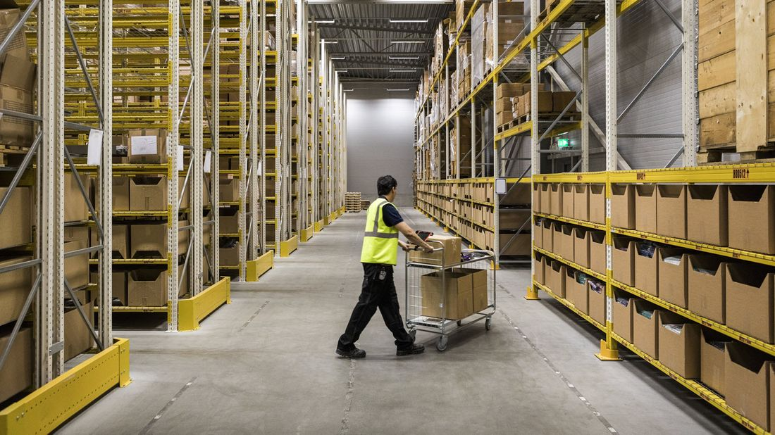 A warehouse worker at risk of automation moves goods on cart