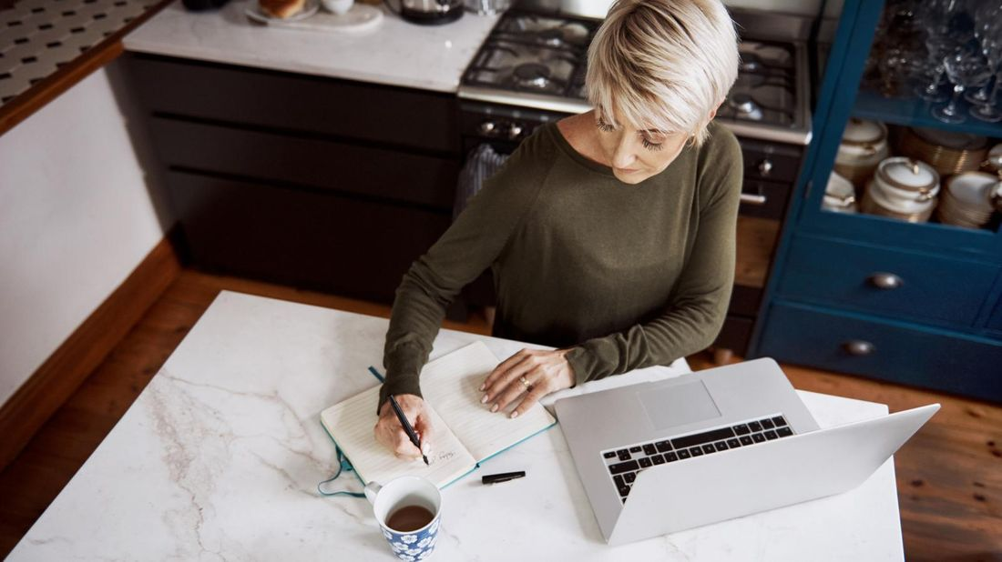 Woman with laptop and notebook prepping financially for a job loss.