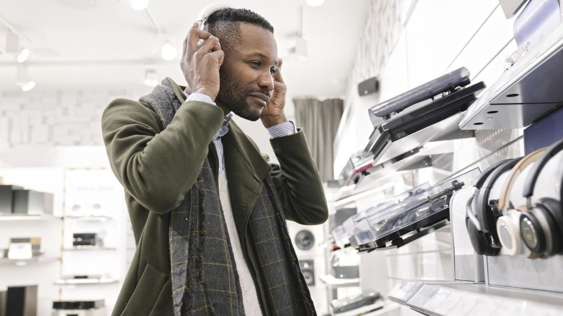 Man trying on headphones in a store in March