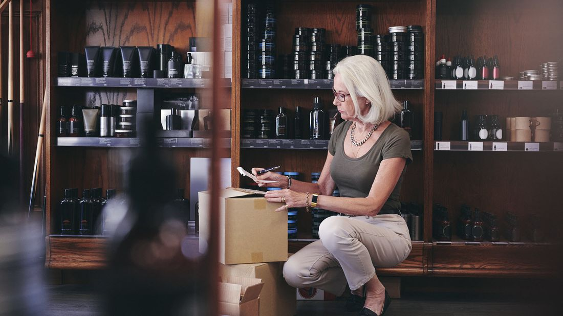 Woman kneeling down and looking at her small business financial wellness checklist.