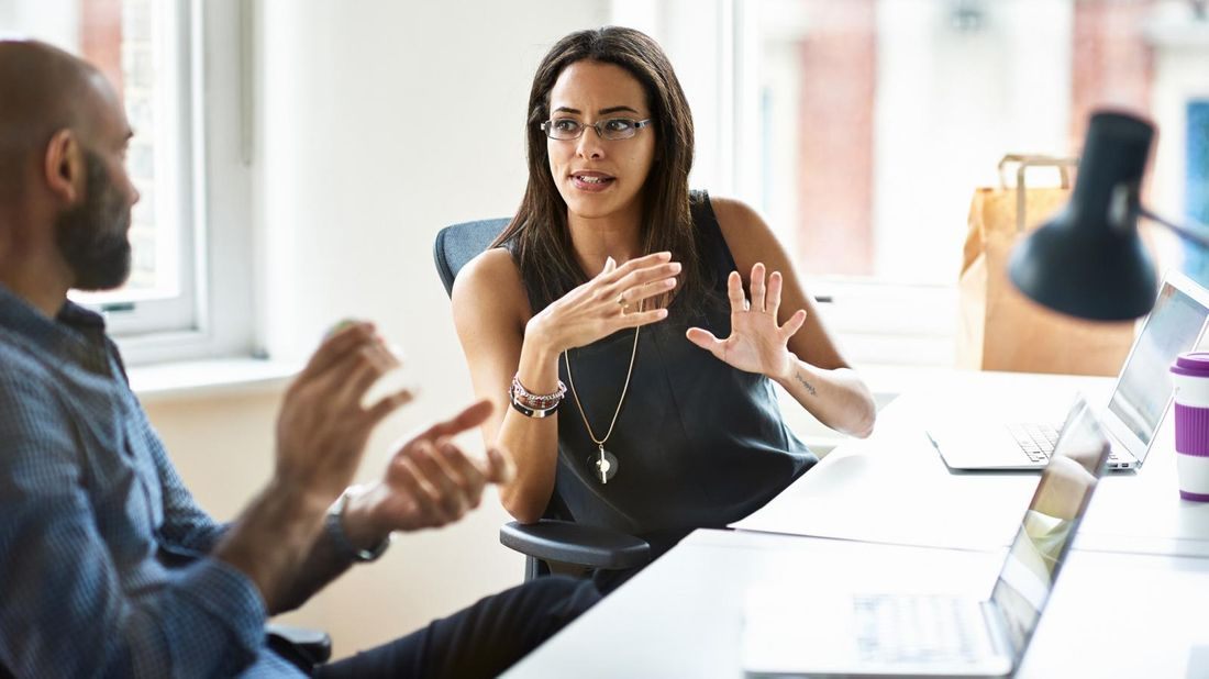 Man and woman at table discussing manager holding you back