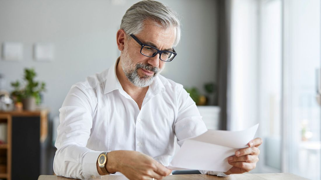 man reading letter at home