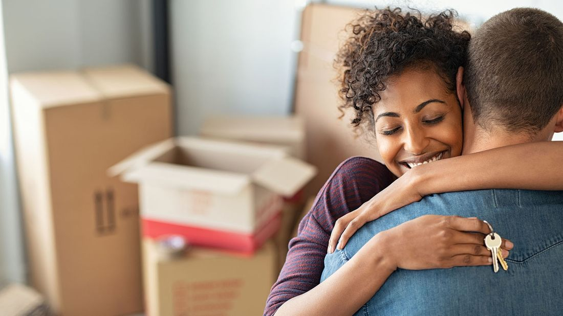 woman hugging man while holding home keys