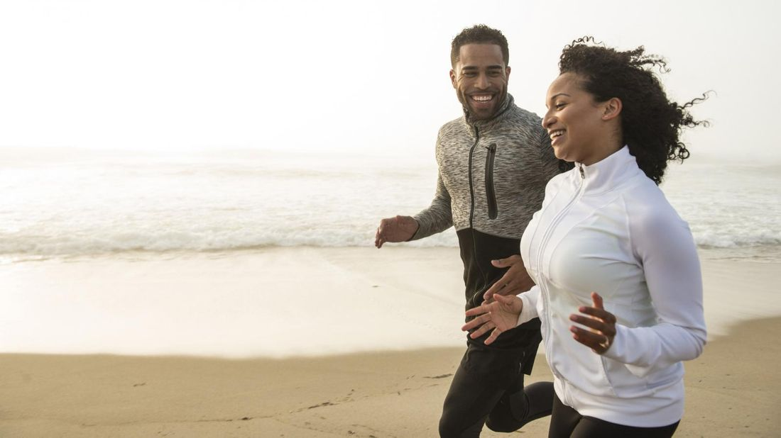 Man and woman jogging side by side on beach