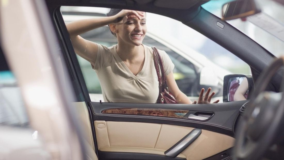 woman-looking-into-car-on-dealer-lot
