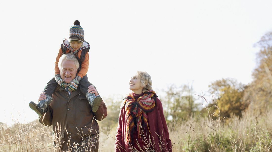 Man and woman walking with their grandchild as they discuss the pros and cons of gifting an estate before death