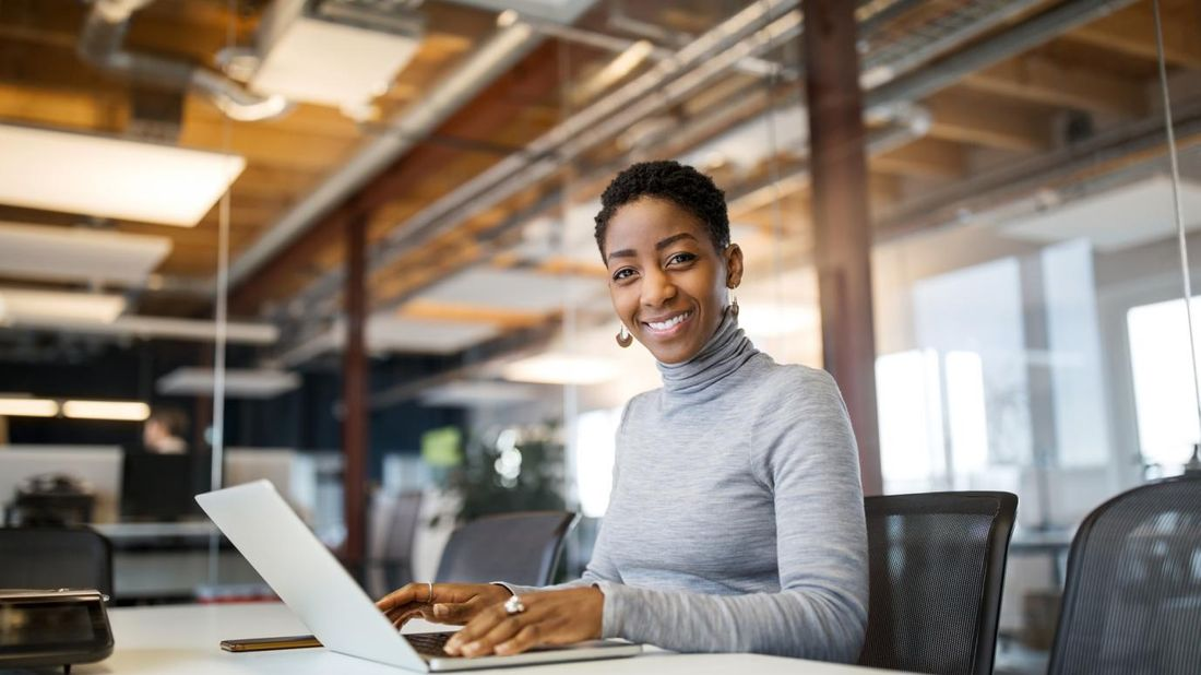 Woman smiling at camera and using laptop