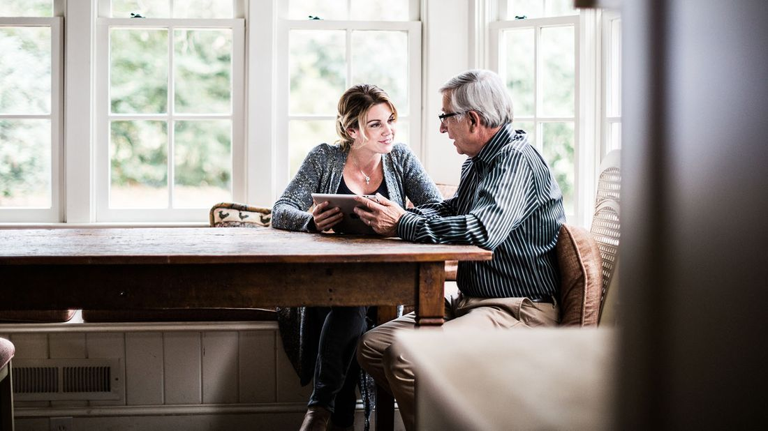 adult daughter and father sitting at home using a tablet