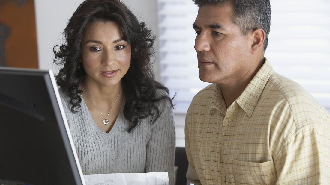 Couple using loan term calculator to compare different loans.