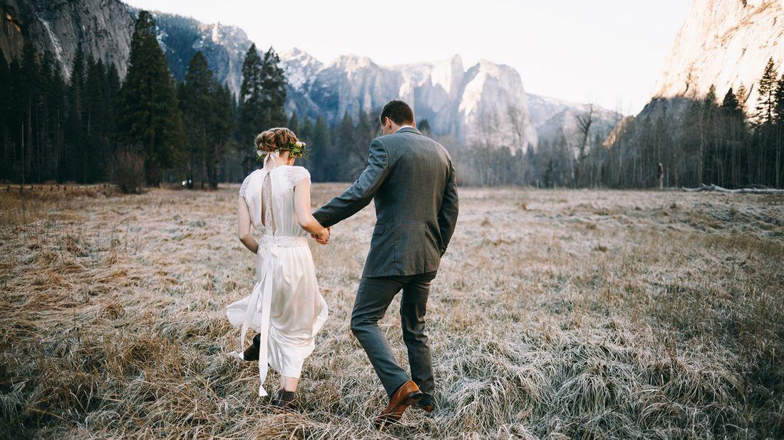 newlyweds walking toward mountains