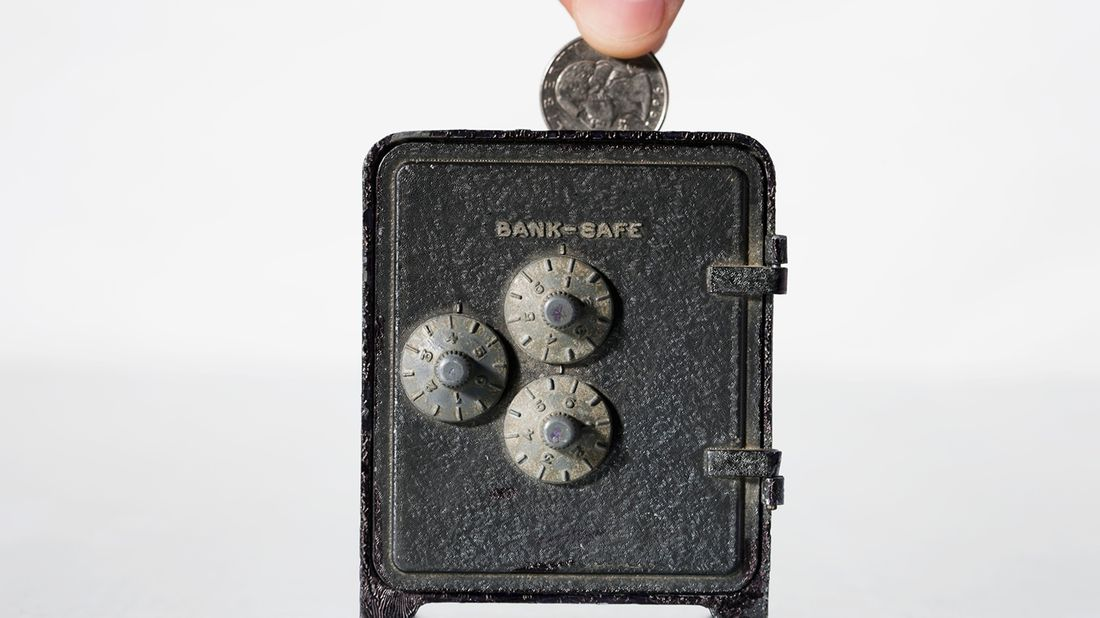 Fingers putting change in a bank safe