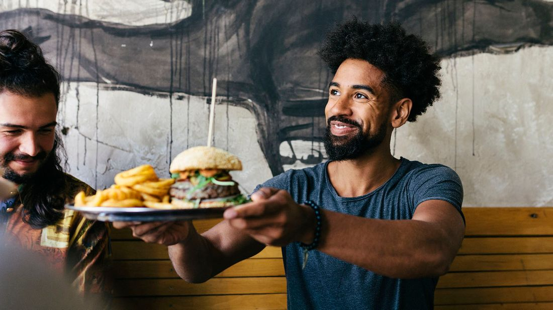 man eating burger in restaurant