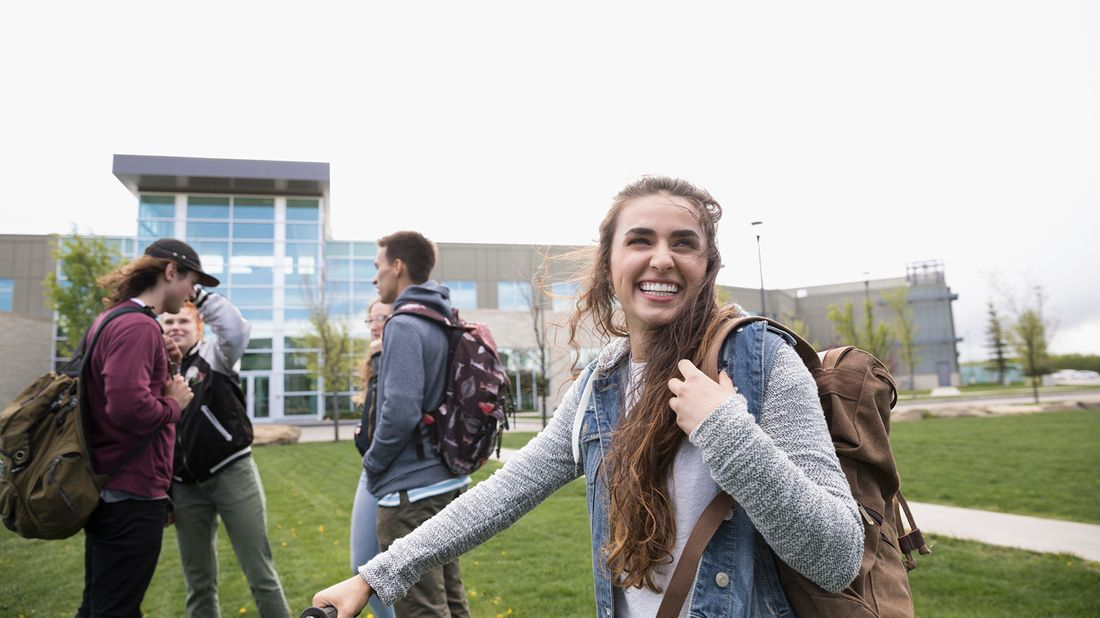 Young female college student smiling and walking on campus.