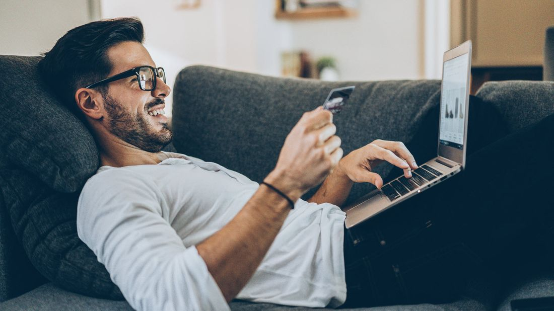 Man laying on a couch making an online purchase.