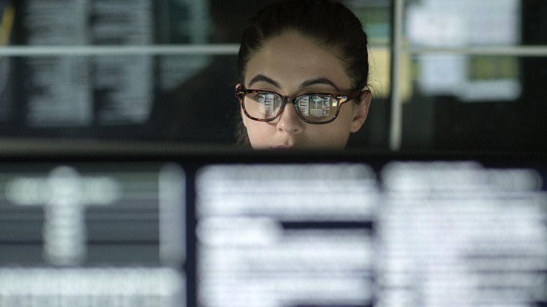 Woman looking at computer screens.