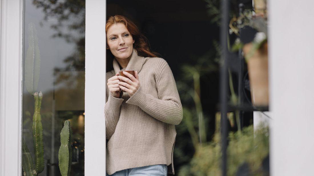 Woman standing at door with coffee mug.