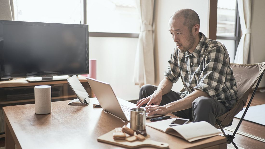 Man working at home and reading Northwestern Mutual Market Commentary