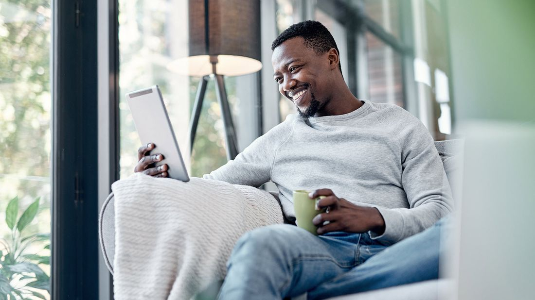 Man drinking coffee and reading Northwestern Mutual Market Commentary