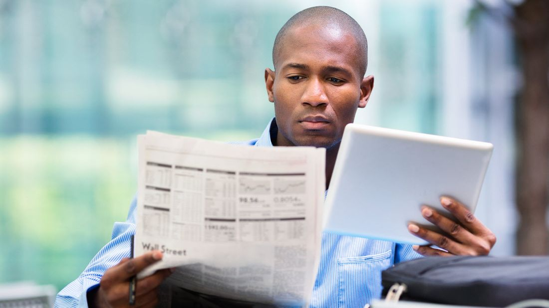 Man looking at stock market news in a newspaper and on a tablet.