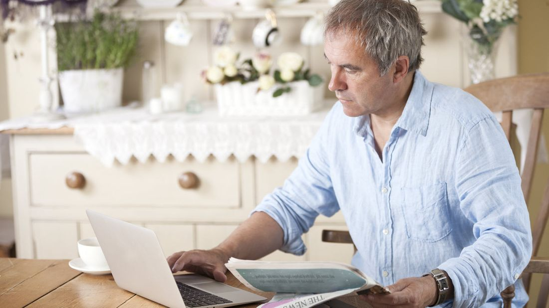 Man sitting at table reading Northwestern Mutual Market Commentary