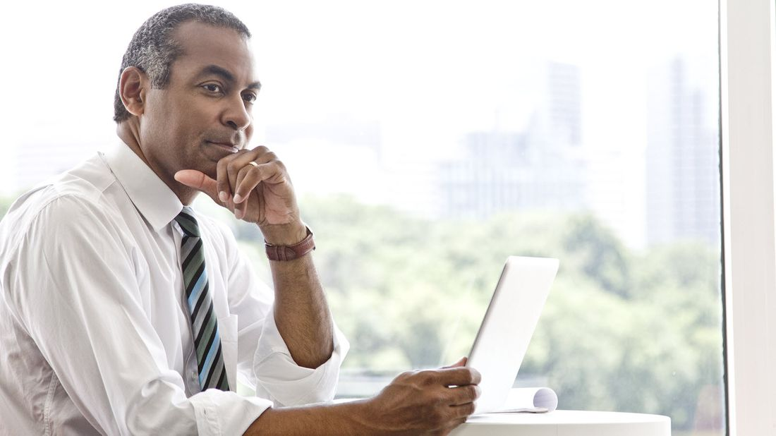Businessman at a computer reading Northwestern Mutual Market Commentary